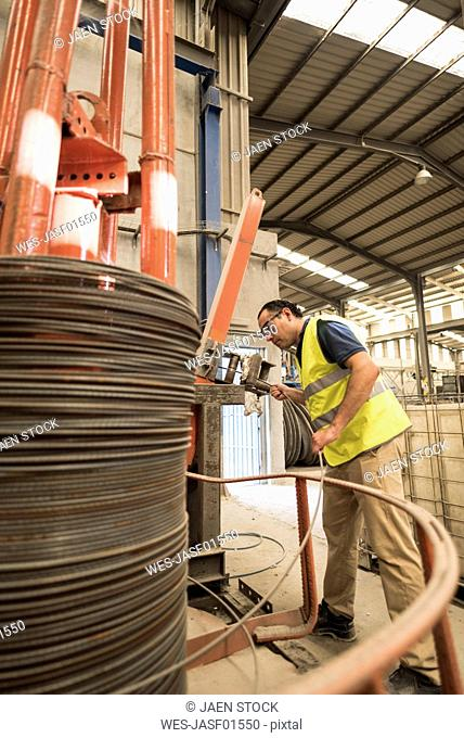 Worker in concrete factory puttinf steel into wire braiding machine