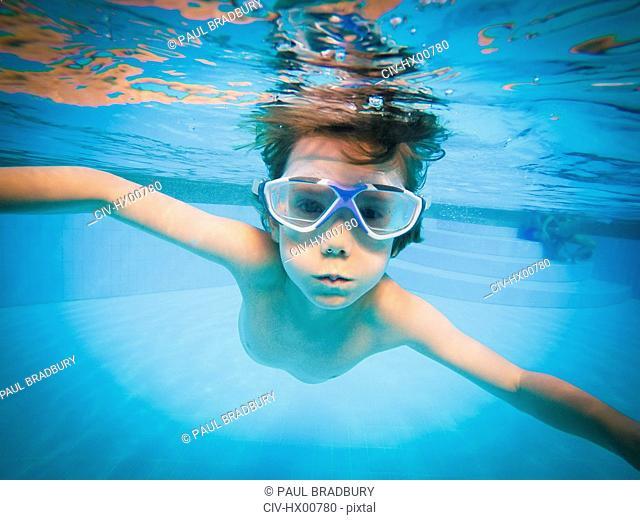 Portrait of boy swimming underwater in swimming pool