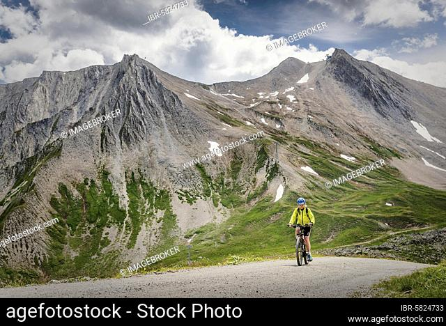 Mountain biker rides on alpine gravel road, Serfaus, Tyrol, Austria, Europe