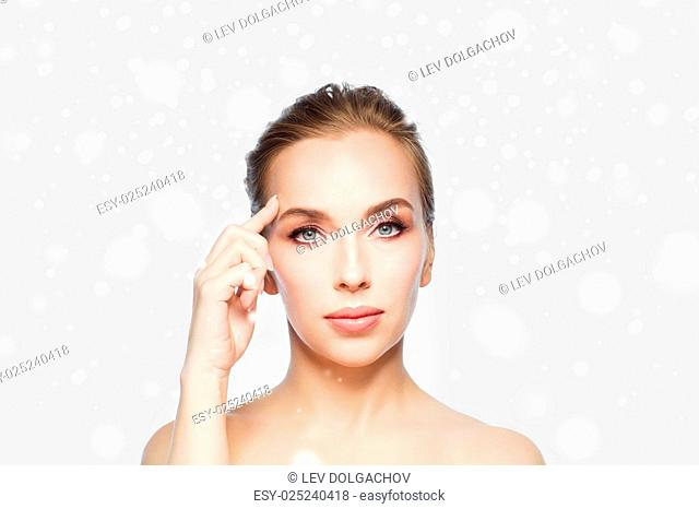 beauty, people, winter and plastic surgery concept - beautiful young woman showing her forehead over gray background and snow