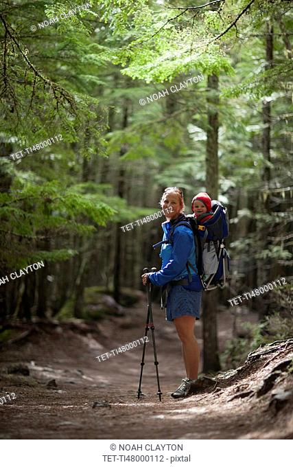 Woman with son (4-5) on trail of cedars