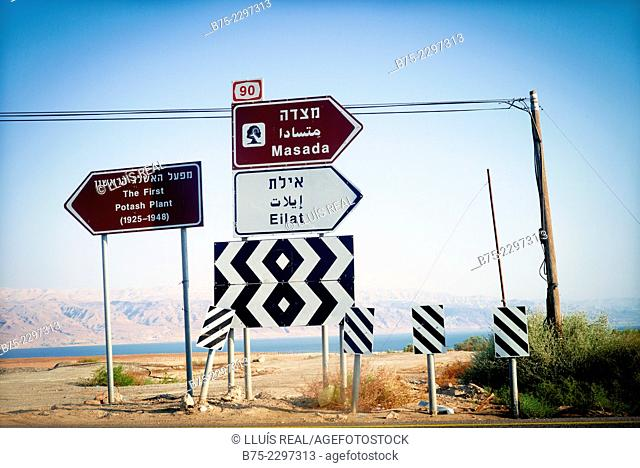 View of a several road signs indicating different places: Masada, Eilat and the first Potash Plant (1925-1948), with the Death sea on the background, Israel