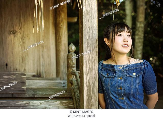 Young woman wearing blue dress at Shinto Sakurai Shrine, Fukuoka, Japan