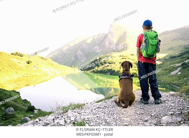Austria, South Tyrol, young boy standing next to his dog