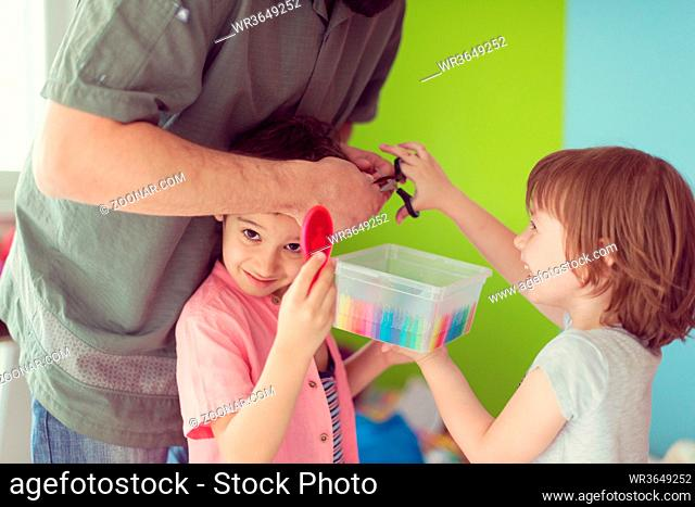 sister and brother havin fun and play hairstylist game at home with father