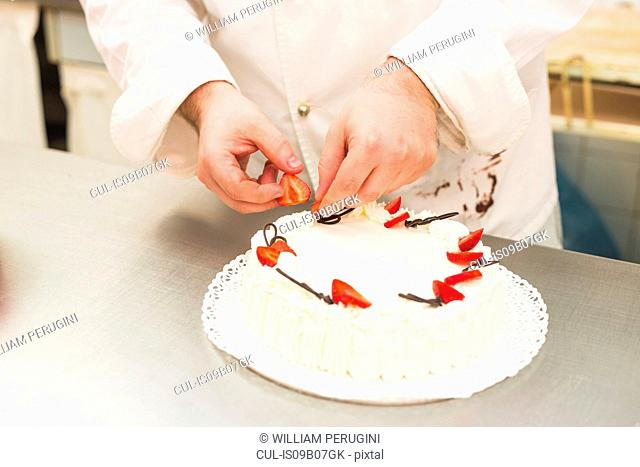 Baker decorating cake with strawberries