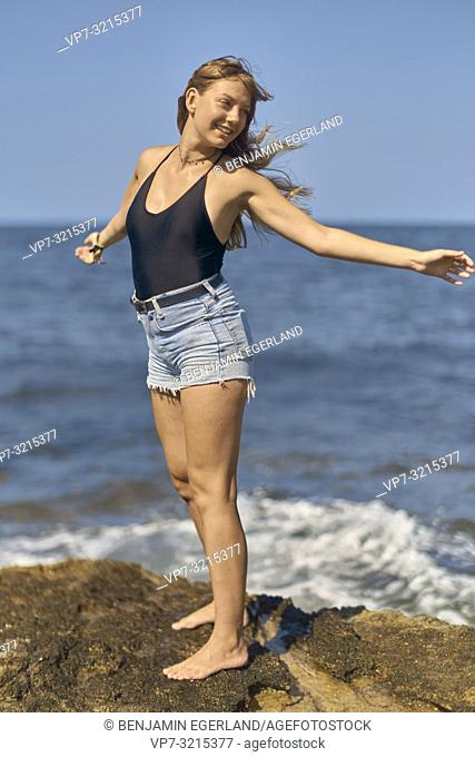 young woman stretching arms in wind at seaside, enjoying summer holiday and freedom, in Crete, Greece
