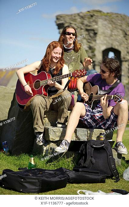 Aberystwyth university students playing guitars outdoors on a summer afternoon at the end of term after exams are finished, Wales UK
