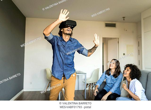 Two women watching man with VR glasses at home