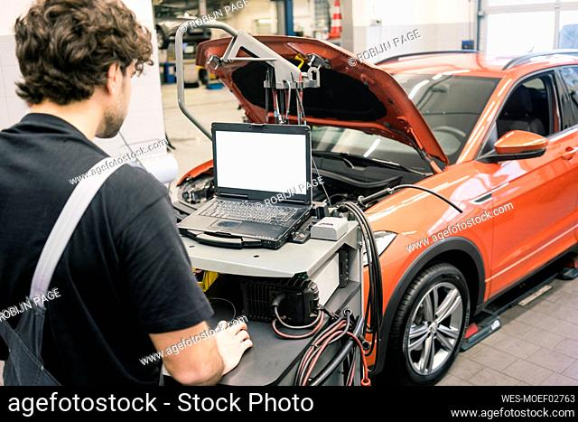 Car mechanic in a workshop using modern diagnostic equipment
