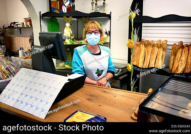 A woman wears a protective mask in a small bakery in the south of France