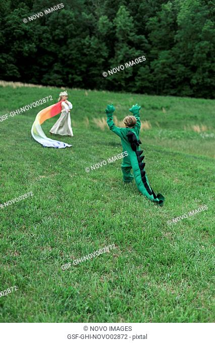 Young Boy in Dragon Costume Playing with Young Girl in Princess Costume in Grassy Field