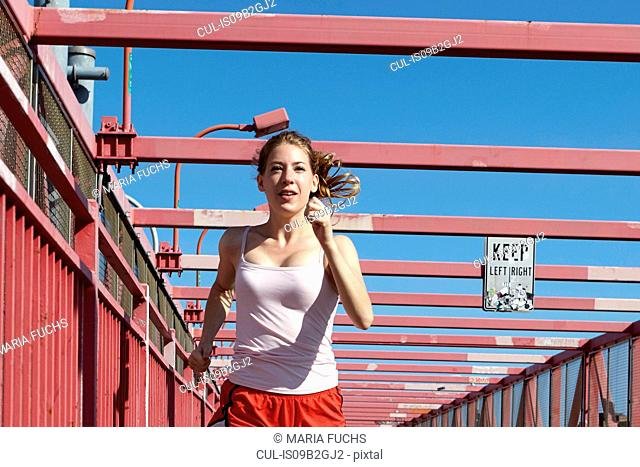Young woman exercising outdoors, running