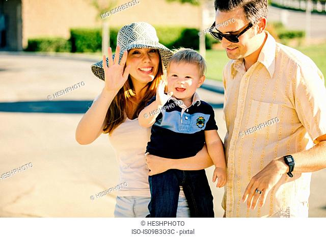 Young family standing together outdoors, mother and young son waving