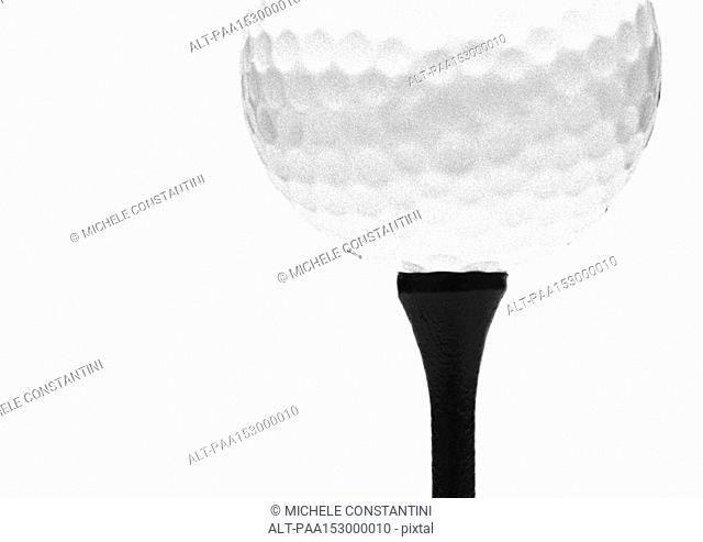Golf ball on tee, close-up, b&w