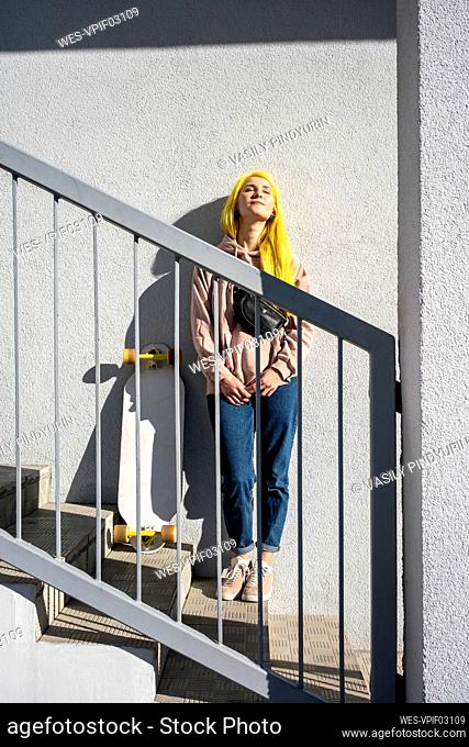 Thoughtful woman standing on steps during sunny day