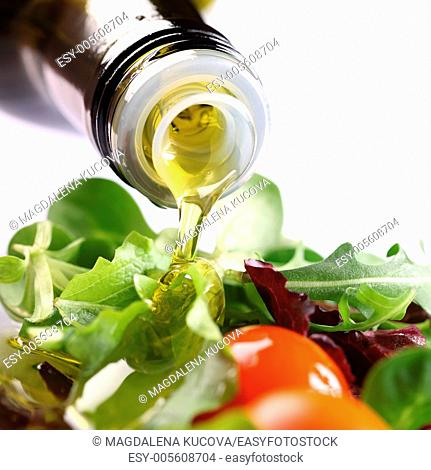 Close-up of olive oil pouring on salad