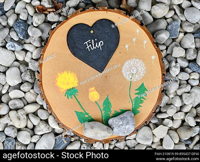 """19 August 2021, Brandenburg, Burg: A painted wooden memorial disc with a heart and the name """"""""Filip"""""""" can be seen at the children's hospice """"""""Pusteblume"""""""" run..."""