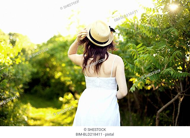 Caucasian woman holding hat on rural path