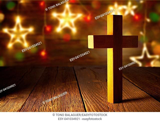 Christian wood cross on Christmas stars wooden background