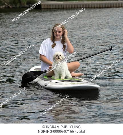 Teenage girl sitting on paddleboard with puppy, Lake of The Woods, Ontario, Canada