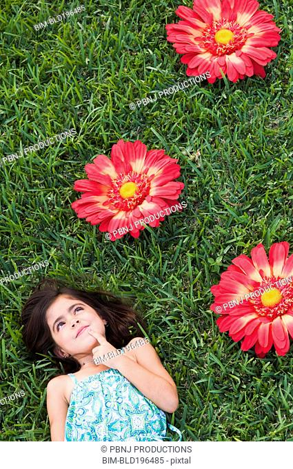 Mixed race girl laying in grass next to large flowers
