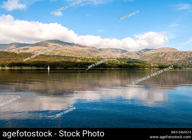 Coniston Water in the Lake District in England on a beautiful quiet morning during early autumn. A single white sailing boat is on the horizon and the Coniston...