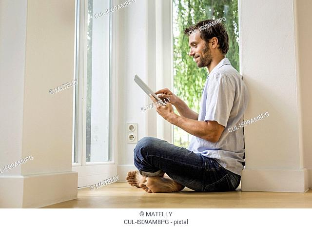 Mid adult man using touchscreen on digital tablet in sitting room