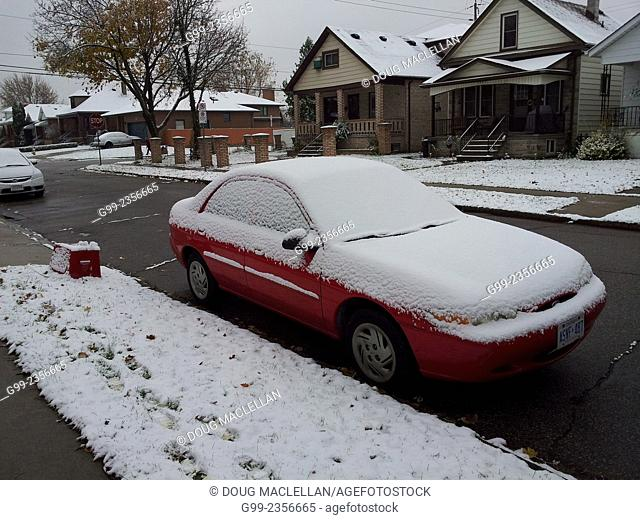 A red car and red recycling box on a residential street during the first snow fall of the season, Windsor, Ontario, Canada