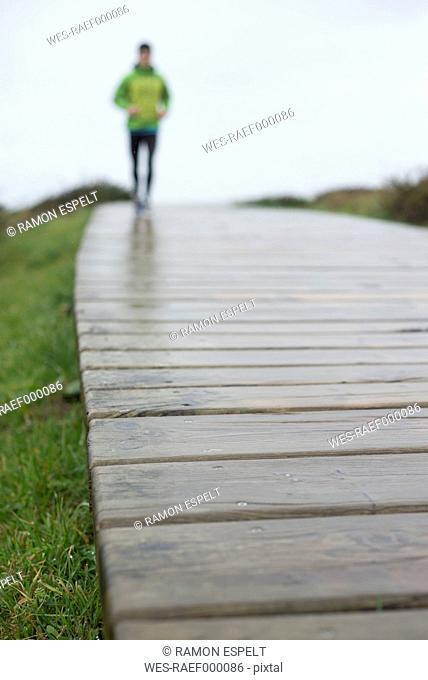 Spain, Valdovino, defocused man running on a boardwalk at a rainy day