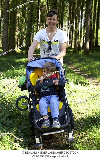 father with buggy and toddler son walking in forest, in Herrenchiemsee, Chiemsee, Bavaria, Germany