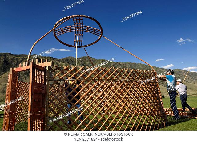 Three men setting up a yurt frame in pasture of Chilik river valley Saty Kazakhstan