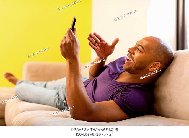 Mid adult male on sofa using digital tablet