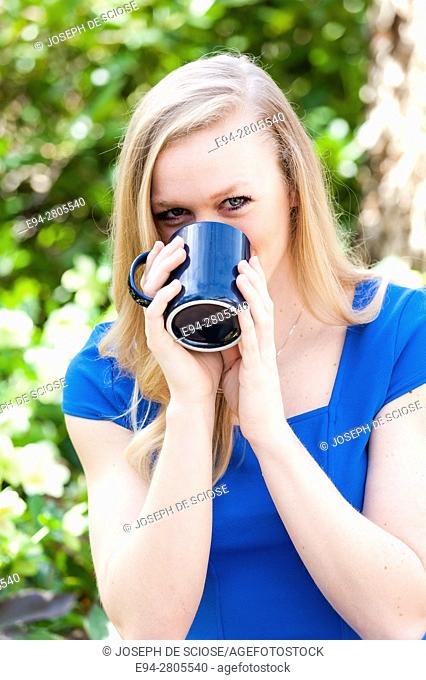 A 25 year old blond woman holding a coffee mug in front of her face, looking at the camera, outdoors