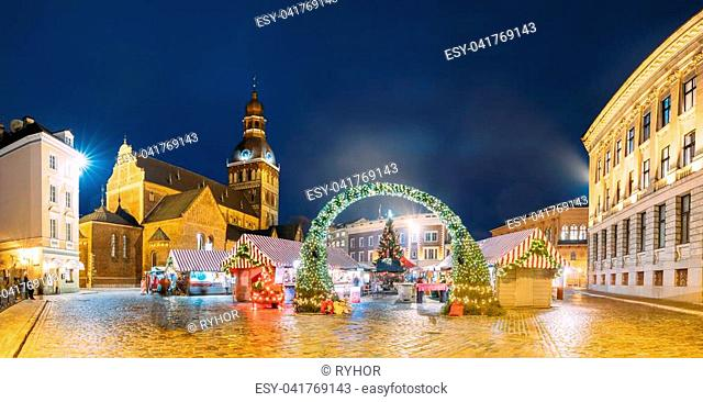 Riga, Latvia. Panorama Of Xmas Market On Dome Square With Riga Dome Cathedral. Christmas Tree And Trading Houses. Famous Landmark At Winter Evening Night In...