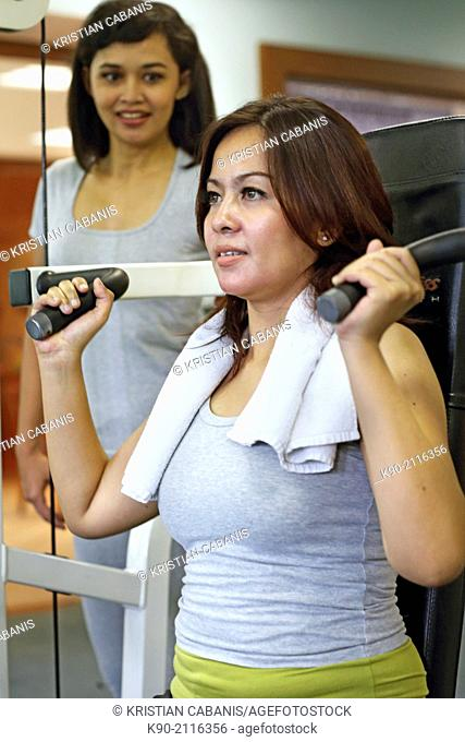 Two asian women doing weightlifting at a machine, Jakarta, Indonesia, Southeast Asia