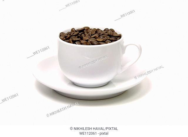 Ceramic coffee cup filled with beans