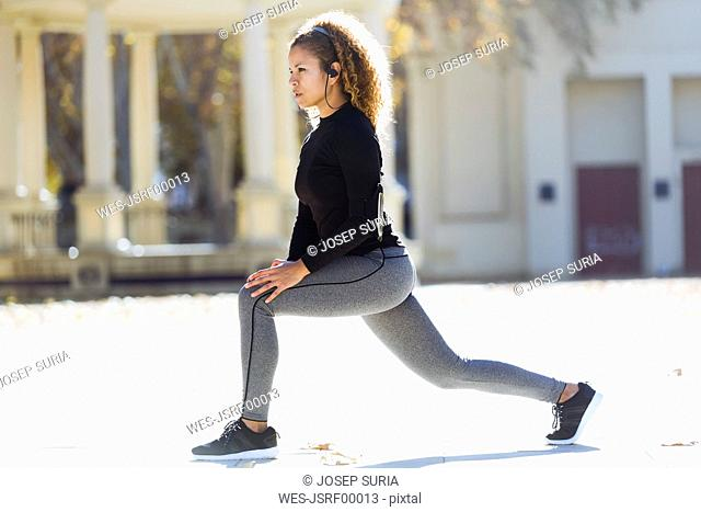 Young woman with earphones stretching