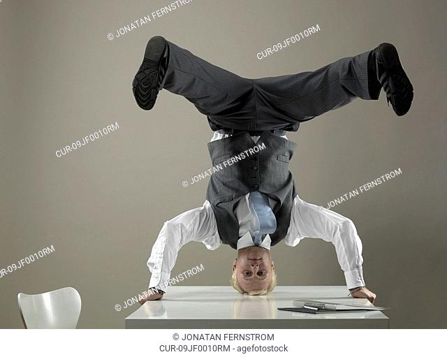 Business man standing on head on table