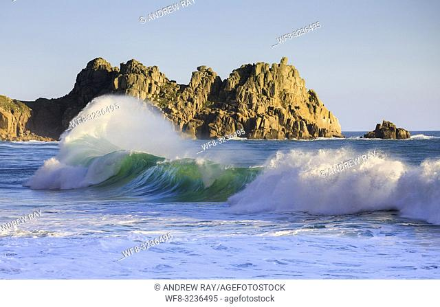 A breaking wave captured using a telephoto lens from Porthcurno Beach on Cornwall's Penwith Peninsula, with Logan Rock in the distance