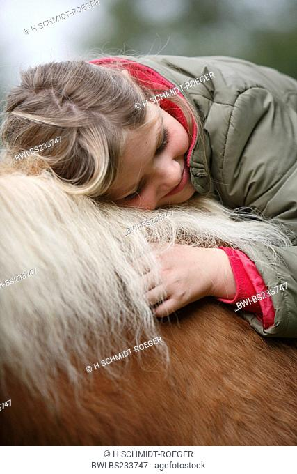 domestic horse Equus przewalskii f. caballus, girl sitting on a horse smiling while laying her head on its mane, Germany