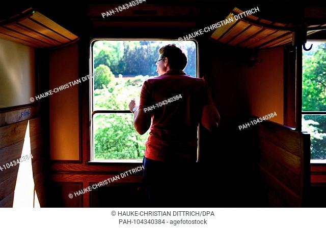 A man looks out of a historic railroad waggon at Minett Park Fond-de-Gras near Niedercorn (Luxemburg), 06 May 2018. | usage worldwide