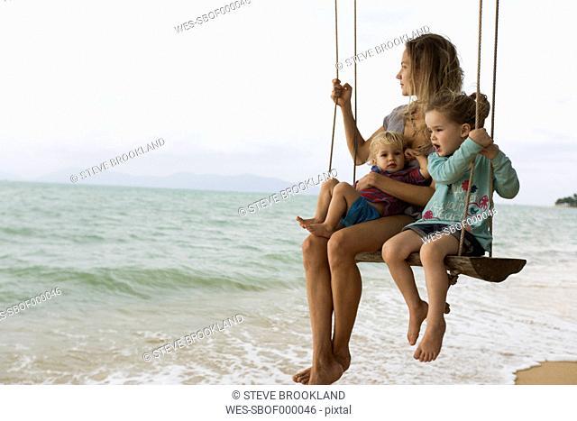 Thailand, family on beach on swing