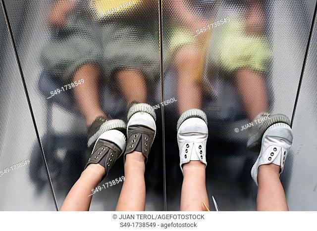 Boy's legs in elevator, detail
