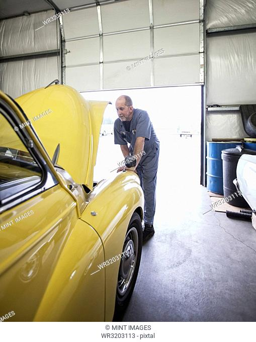 A mechanic looking under the bonnet of a bright yellow Morris Minor English classic car