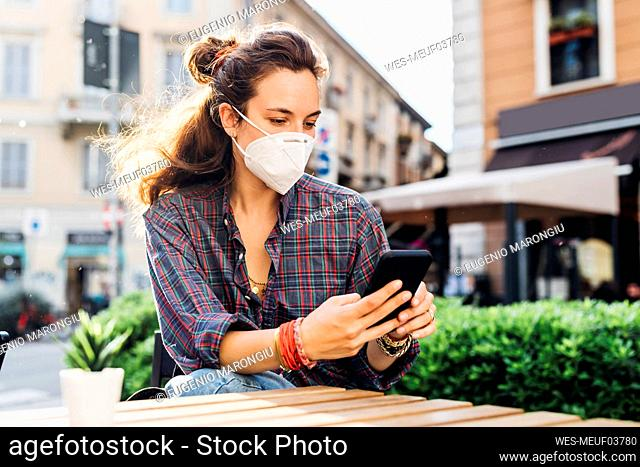 Woman with protective face mask using mobile phone at sidewalk cafe on sunny day