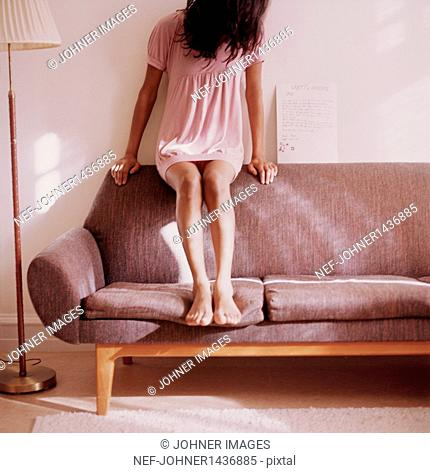 Teen girl sitting on sofa
