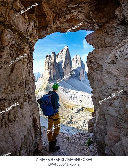 Hiker at the via ferrata to the Paternkofel, view from war tunnel, north faces of the Three Peaks of Lavaredo, Sexten Dolomites, South Tyrol, Italy