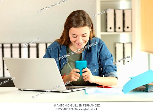 Front view portrait of a distracted intern reading messages in a smart phone at office