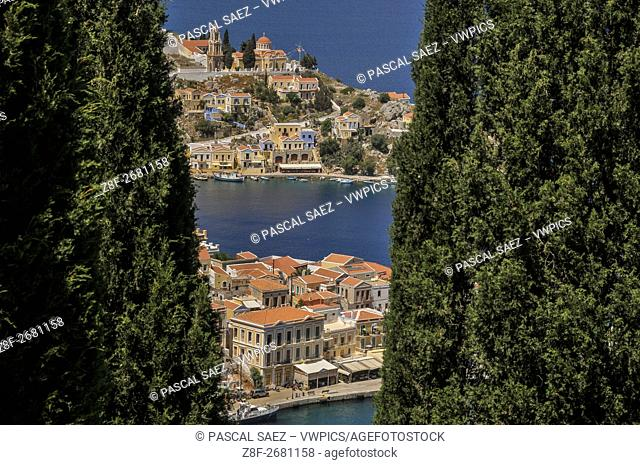 Partial view of Symi Town and its harbour seen through cypress tress from a hill above. Symi Town is the main settlement on the island of Symi